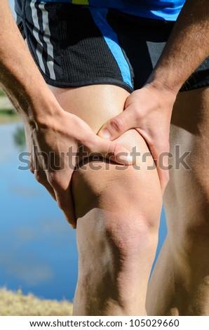 Runner leg injury grabbing knee. Quadriceps pain with caucasian male athlete. - stock photo