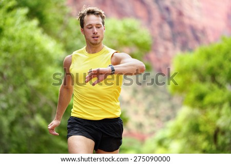 Runner looking at heart rate monitor smartwatch while running. Man jogging outside looking at his sports smart watch during workout training for marathon run. Fit male fitness model in his 20s. - stock photo