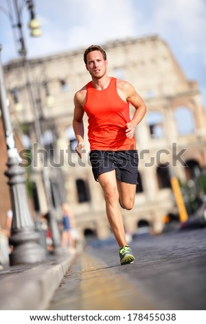 Runner - man running by Colosseum, Rome, Italy. Male athlete training for marathon jogging in city of Rome in front of Coliseum in full body length. Fit male sport fitness model jogger in run outside. - stock photo