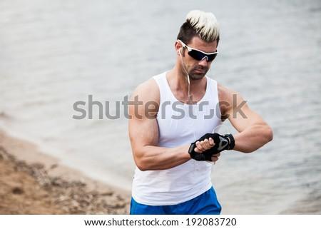 Runner man running with heart rate monitor on beach - stock photo