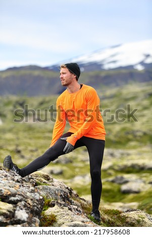 Runner man stretching legs after running in cross country trail run. Fit male runner exercise training outdoors in beautiful mountain nature landscape with Snaefellsjokull, Snaefellsnes, Iceland. - stock photo