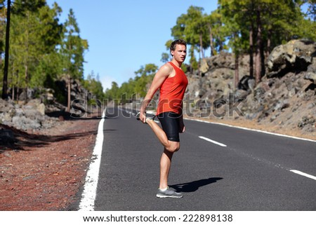 Runner man stretching thigh and legs after running on mountain forest road in. Handsome Caucasian male fitness model outdoors. - stock photo
