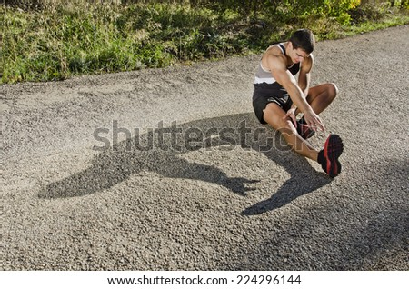 Runner man warming arms with sun light shadow, warm up and stretching - stock photo
