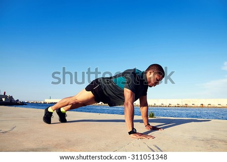 Runner man with a muscular body doing push-ups on concrete pier against blue sky background with copy space area for your text message or content, strong male engaged in physical activity outdoors - stock photo