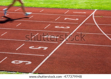 Runner on a running track finishing a race first (motion blurred image)
