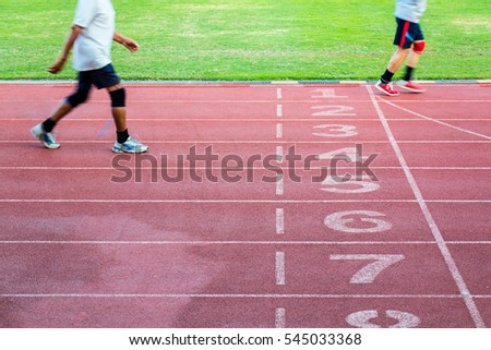 Runner on a running track (motion blurred image). jogging and exercise in running track. people running on stadium track.