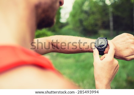 Runner on mountain forest trail checking looking at stopwatch smart watch, cross country runner checking performance, GPS position or heart rate pulse. Sport equipment in use outdoors on summer trail - stock photo