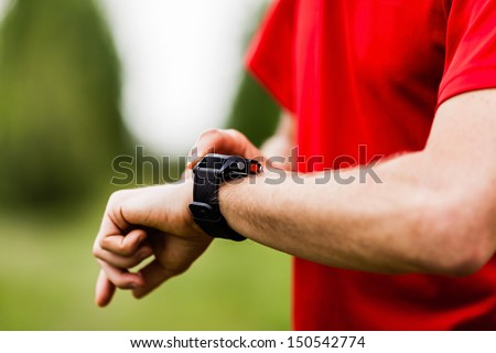 Runner on mountain trail looking at sports smart watch, checking performance or heart rate pulse trace. Sport and fitness outdoors in nature. - stock photo