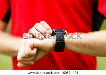 Runner on mountain trail looking at sportwatch smart watch, checking performance or heart rate pulse tracing. Sport and fitness outdoors in nature. - stock photo