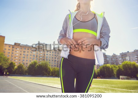 Runner on the stadium track. Woman summer fitness workout. Jogging, sport, healthy active lifestyle concept