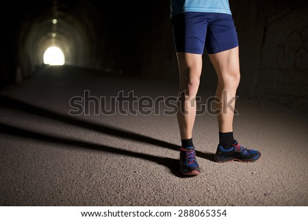 Runner posing inside a tunnel with ambient light, legs detail