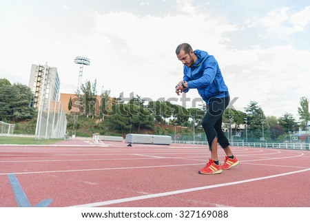 Runner ready to run is looking at his watch on track field
