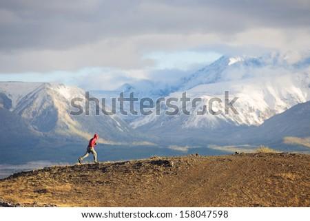 Runner rugged mountain terrain - stock photo