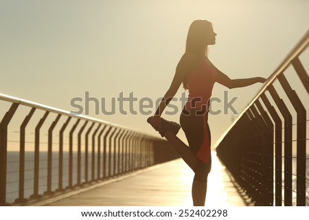 Runner silhouette doing stretching exercises at sunset in a bridge on the beach - stock photo
