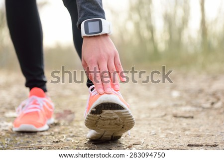 Runner stretching leg before run. Closeup of running shoes of a female jogger touching toe wearing a wearable tech - sportswatch activity tracker or smartwatch used as a heart rate monitor for cardio. - stock photo