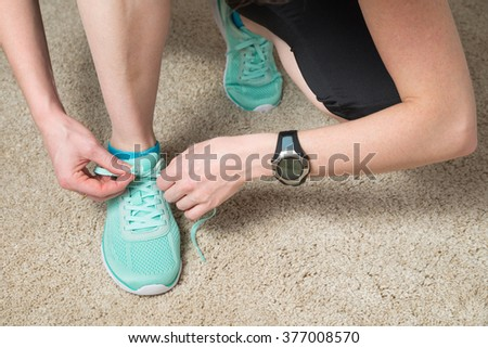 runner tying laces wearing heat rate monitor and activity tracker for cardio exercise - stock photo