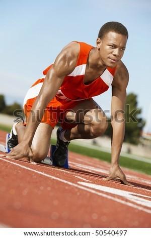 Runner Waiting in Starting Block - stock photo