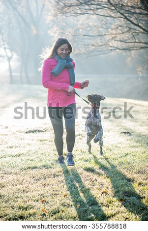 Runner woman and her cute German pointer dog running together outdoor at the beautiful park. Healthy life concept. - stock photo