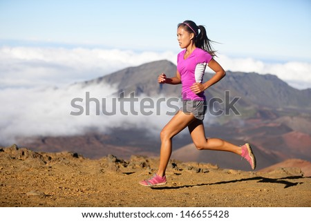 Runner woman athlete running sprinting fast. Female sport fitness model training a sprint in amazing nature landscape outdoors at speed wearing sporty runners clothing outfit. Mixed race Asian woman - stock photo