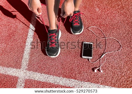 Runner woman athlete tying running shoes laces getting ready for race training on run track with smartphone and earphones for music listening on mobile phone.