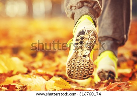 Runner woman feet running on autumn road closeup on shoe. Female fitness model outdoors fall jog workout on a road covered with fallen leaves. Sports healthy lifestyle concept. - stock photo