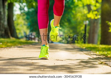 Runner woman feet running on road closeup on shoe. Female fitness model sunrise jog workout in a sunny park outdoors. Sports healthy lifestyle concept.