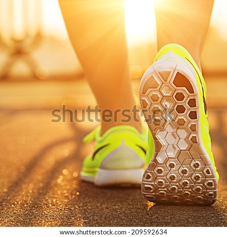Runner woman feet running on road closeup on shoe. Female fitness model sunrise jog workout. Sports healthy lifestyle concept. - stock photo