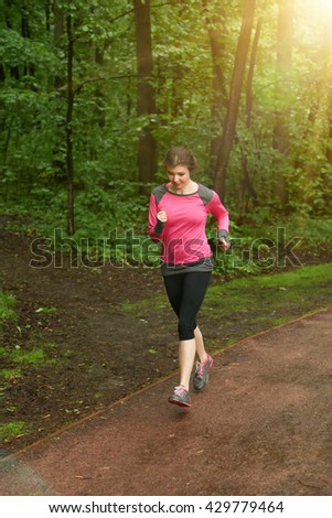 Runner woman jogging in summer forest. Beautiful young fit fitness sport model jogging with slight motion blur.
