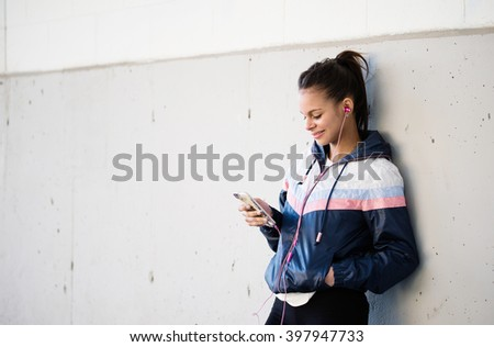 Runner woman listening to music on a break from training