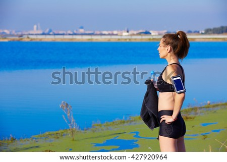 Runner woman relaxing after workout outdoor with water bottle in a lake