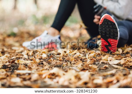 runner woman rest on the leaves in park, focus on shoes - stock photo