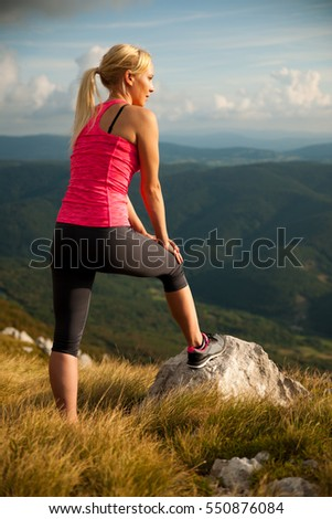 runner woman rests on a mountain top after running workout