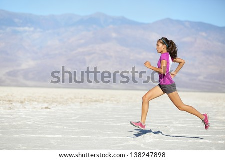 Runner woman running and sprinting on trail run in desert. Female sport fitness athlete in high speed sprint in amazing desert landscape outside. Mixed race Asian Caucasian fit sports model sprinter. - stock photo