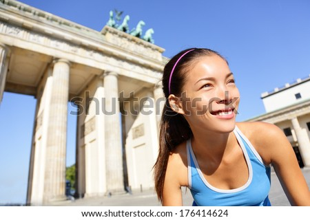Runner woman running in Berlin, Germany by Brandenburg Gate. Athlete jogging living healthy lifestyle. Female runner jogging. Urban fitness girl working out outdoors in jacket. - stock photo