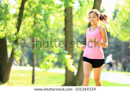 Runner - woman running in city park on sunny summer day with with sunshine in green trees. Asian / Caucasian fitness sports model during outdoor workout. - stock photo