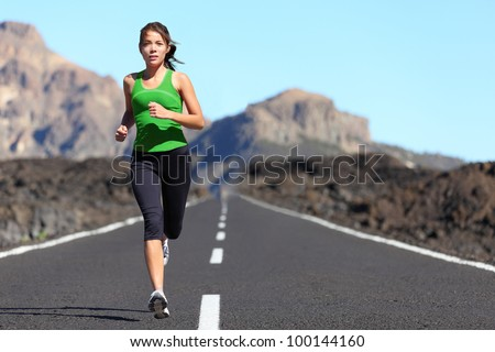 Runner woman running on mountain road in beautiful nature. Asian female sport fitness model jogging training for marathon during outdoor workout. - stock photo