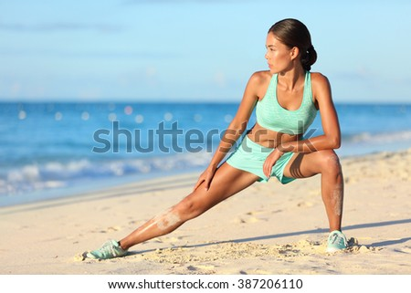 Runner woman stretching legs with lunge hamstring stretch exercise leg stretches. Fitness female athlete relaxing on beach doing a warm-up before her strength training cardio workout. - stock photo