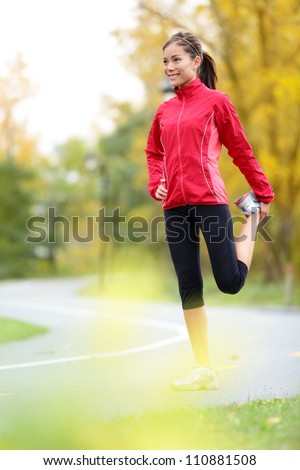 Runner woman stretching thigh after running in city forest park in fall. Beautiful young mixed race Asian / Caucasian female fitness model in autumn color.