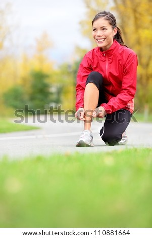 Runner woman tying running shoes outside in fall. Beautiful young fitness model smiling happy in casual jogging clothing. - stock photo