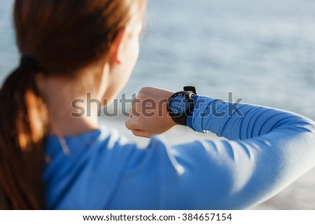 Runner woman with heart rate monitor running on beach - stock photo