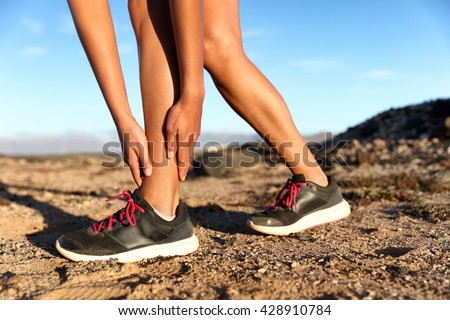 Runner woman with hurt ankles in pain during marathon. Athlete woman running outside with body injury. Sprained ankle on trail run in summer outdoors nature. Fitness leg accident on cardio workout. - stock photo