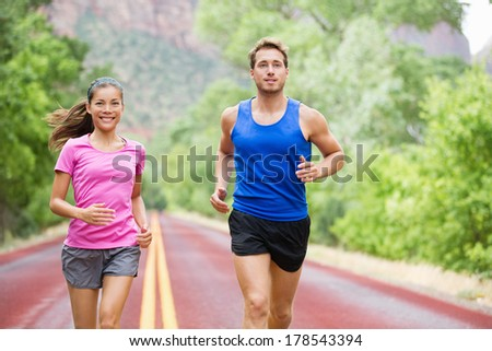 Runners couple in jogging exercise outside on road in beautiful nature training for marathon run. Multiracial sports couple, Asian woman sport model and man fitness model exercising smiling happy. - stock photo