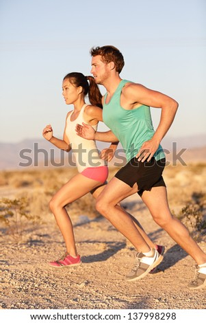 Runners couple running in trail run. Runner man and sport woman training and jogging outside in cross country run outside at summer sunset. Fit male Caucasian fitness model and Asian female runner. - stock photo