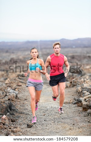Runners couple running on trail in cross country run outdoors training for marathon or triathlon. Fit young fitness model man and asian woman training together outside on Big Island, Hawaii, USA. - stock photo