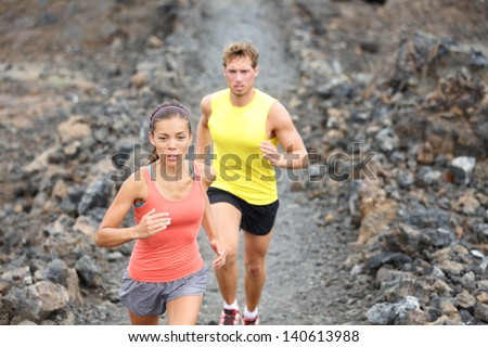 Runners couple running on trail in cross country run outdoors training on Hawaii, Big Island for marathon or triathlon. Fit young fitness model man and asian woman training together outside. - stock photo