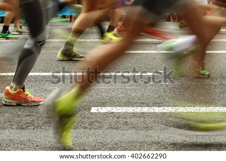 Runners feet on the road in blur motion during a long distance running event