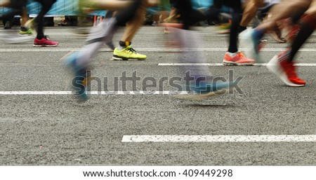 Runners feet on the road in blur motion during a long distance running event - stock photo
