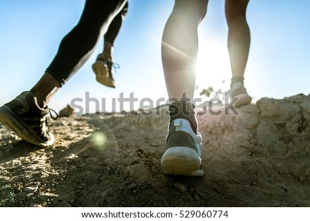 Runners jogging outdoors, closeup on shoes
