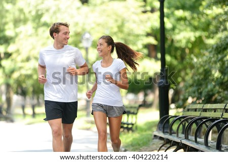 Runners jogging together in New York City Central Park, USA. Healthy couple of new yorkers athletes friends running in summer sun working out a cardio exercise on Manhattan, United Sates of America. - stock photo