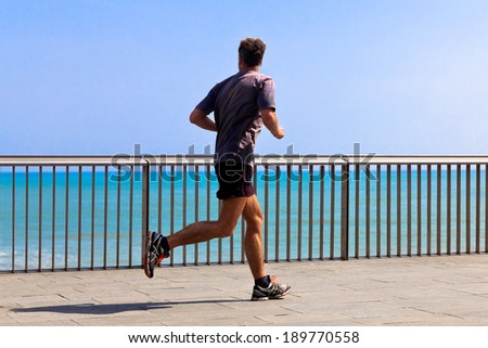 Runners on the beach. Urban scene. - stock photo